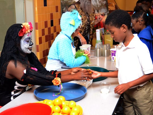 Circle of Red Volunteer LaTonya Charles helps Julius Patrick Elementary student Broderick Clark, 9, peel an orange as he makes a candy corn parfait at school on Thursday, October, 30, 2014. --Tia Owens-Powers/ towens@thetowntalk.com