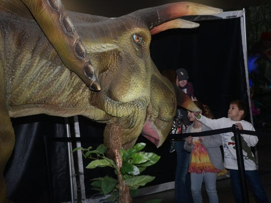 "ANI Discover the Dinosaurs Patton Ferguson (right) and his cousin Isabella McLain (left0 touch a replica of a triceratops at Blue Star Media's ""Discover the Dinosaurs"" exhibit held Saturday, Nov. 23, 2014 at the Alexandria Riverfront Center in downtown A"
