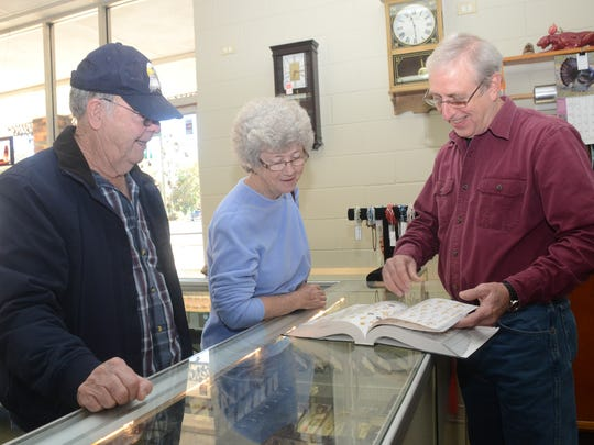 ANI Shopping Friday Shane Ward (right), owner of Ward's Jewelry, helps Leon Anderson (far left) and his wife Ernestine Anderson of Jena look for items in a catalog Friday, Nov. 28, 2014. -Melinda Martinez/mmartinez@thetowntalk.com, The Town Talk, Gannett