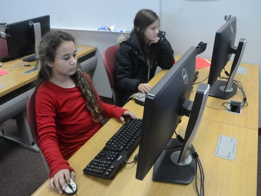 ANI Country Day Country Day School sixth-graders Amira Benghozi (left) and Mikayla Bayonne work on reports about the Plain Indians Wednesday, Dec. 10, 2014. The school is offering Microsoft programs for free to students and parents on up to five devices.-M