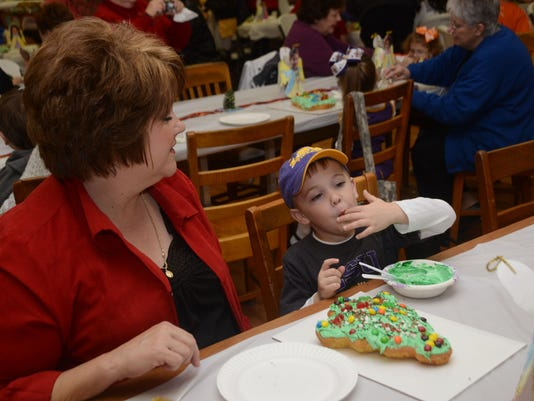 ANI Cake Decorating Denise Cobb (left) watches grandson Matthew Cobb lick frosting off his fingers as they decorate a Christmas cake Thursday Dec. 17, 2014.-Melinda Martinez/mmartinez@thetowntalk.com The Town Talk, Gannett