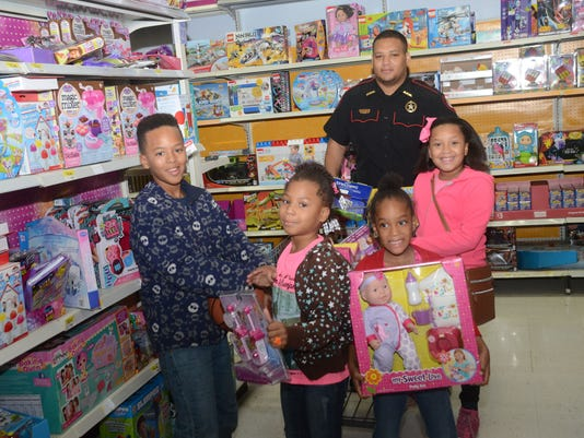 ANI Shop with a Cop Glen Taylor Jr. (far left) and his sisters Marriana Taylor, Tatyana Taylor and Shania Taylor shop for Christmas presents at the Wal-Mart on North Mall Drive with Alexandria City Marshal Deputy Derrick Stafford during the annual City of