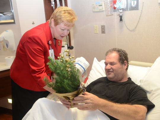 Lane Harrington, chief nurse executive at Christus St. Frances Cabrini Hospital, hands patient Robbie Hall a small Christmas tree on Tuesday.