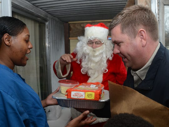 Grant Parish Sheriff Steven McCain (right) hands Lawan Brice a Christmas meal for her family while the sheriff's office was handing out Christmas gifts to those in need throughout Grant Parish Tuesday.