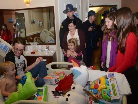 One-year-old Cohen Fusilier (far left), a patient at Rapides Women's and Children's Hospital, and his mother, Emmy Fusilier, receive gifts from Louisiana State Police Troop E troopers and family members Wednesday. Grace Higgins (far right), Jillian Covington (second from right), Reagan Webb, Aaron P. Raines and Trish Raines were among the troopers and family members delivering gifts to young patients at area hospitals.