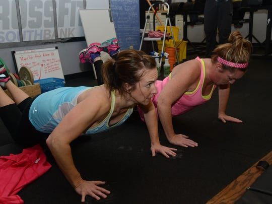 "Monica Nobles (left) and Shelli Heard perform 100 push-ups as part of the ""Angie"" workout at CrossFit South Bank Friday. CrossFit South Bank held a workout fundraiser for member Angie Roberts, who is battling breast cancer. The ""Angie"" is a CrossFit workout that consists of 100 pull-ups, 100 push-ups, 100 sit-ups and 100 air squats."
