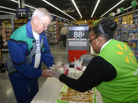 Wal-Mart Neighborhood Market associate Crystal Baines (right) serves cake to Don Sayes at the new Wal-Mart Neighborhood Market on Highway 28 East in Pineville. The store hosted a grand opening Wednesday.
