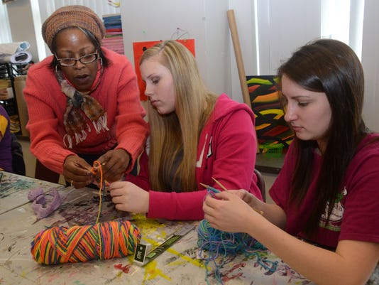 ANI Muse learning to knit Andrea Roberson (far left) helps Daphne Zumwalt (center) and Harli Matt learn how to knit at the Muse Yarn Bombing Knit- In held Saturday, Jan. 10, 2015 at the Alexandria Museum of Art. Members of the Red River Knitters volunteere