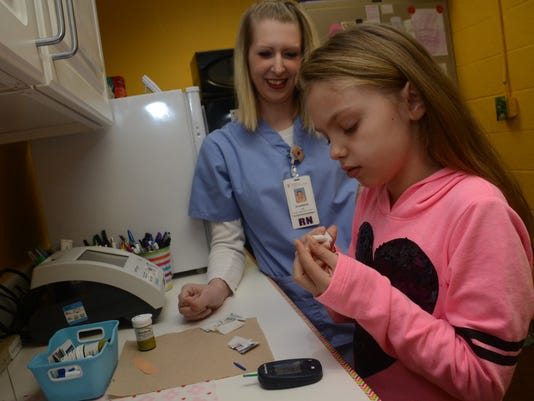 ANI Diabetic Student Lilly Peevy, a diabetic student at Lessie Moore Elementary School in Pineville, checks her blood sugar level under the supervision of Shannon Segura, an RN with the Christus Cabrini School Based Healthcare Center at the school. Friday,