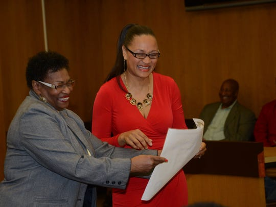 Charlene Rachal (left), a cousin of Monique Rauls (right), presents Rauls with her judgeship commission from Gov. Bobby Jindal on Friday. Rauls was sworn in as the first African-American female judge of the 9th Judicial District Court.