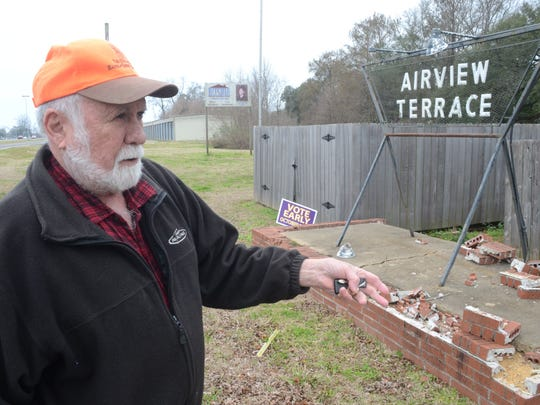 Richard Crooks, a resident of Airview Terrace, talks about the litter problem in Airview Terrace while standing near an the subdivision entrance sign which was destroyed by a traffic accident. He said some motorists passing through the subdivision toss out trash that neighborhood residents have to clean up.