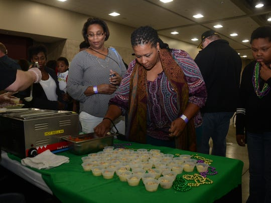Samantha Hargrove (right) and Gena Jones sample shrimp and grits from Atwood's Bakery at the Taste of Mardi Gras on Friday at the Alexandria Riverfront Center in downtown Alexandria.
