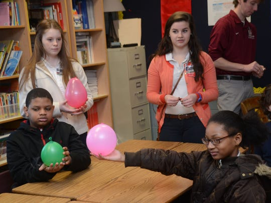 Hannah Aslin (back left) and Sydney Spikes (back right), both juniors at Pineville High School and members of the Pineville High Science Club, help Rosenthal Montessori fourth-graders Joshua Spain (front left), Ciara Owens and Jacob Hale with a science experiment on Wednesday.
