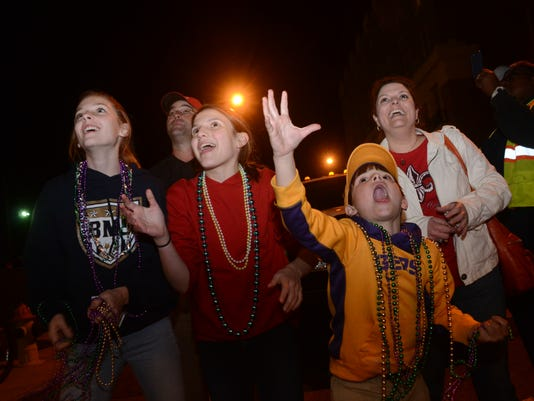 "ANI Night Mardi Gras Parade Hilary Harlow (left), Olivia Hunter, her brother Ian Hunter and mom Shannon Chiasson scream for beads as the first ""Light the Night"" Mardi Gras parade rolls into Alexandria from Pineville Friday, Feb. 6, 2015. -Melinda Martinez"