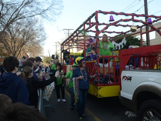 Parade participants hand out throws Saturday at the Alexandria Children's Mardi Gras Parade in downtown Alexandria.