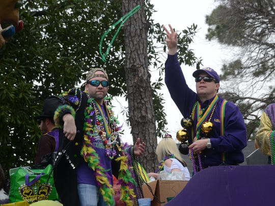 Revelers in the Alexandria Mardi Gras Krewe Parade throws beads to the crowd as it passes by Sunday, Feb. 15, 2015.