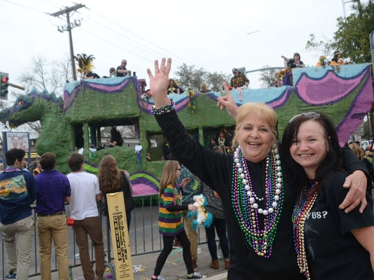 Mildred Newnam (left) and Cindy Ducote have a good time Sunday at the Alexandria Krewe Mardi Gras Parade.