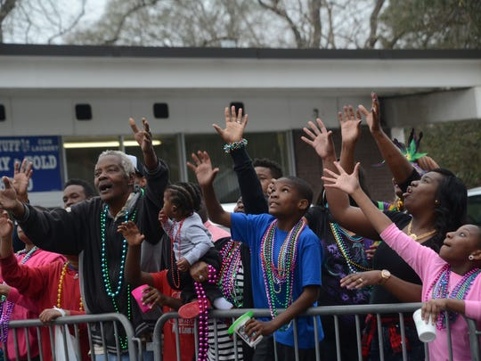 A crowd yells for throws from a float at the Alexandria Krewe Mardi Gras Parade.