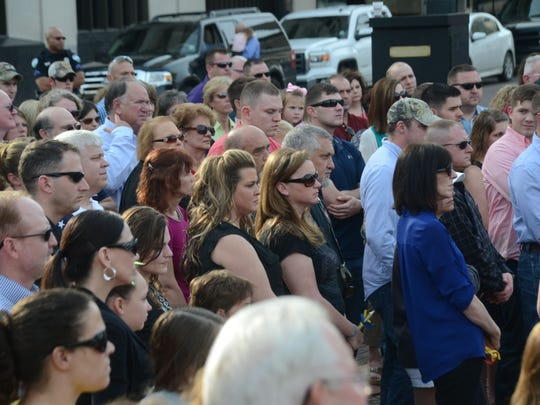 Community members gather for a vigil held Sunday in downtown Alexandria in memory of the 11 service members who lost their lives in a Black Hawk helicopter crash in Florida.