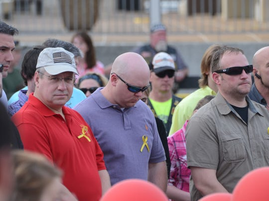 Community members gather for a vigil Sunday in memory of the 11 service members — including David Strother, a 1989 graduate of Pineville High School — who lost their lives in a training mission in Florida.