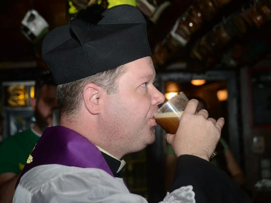 After blessing the beer taps at Finnegan's Wake in downtown Alexandria Tuesday, March 17, 2015, Father Chad Partain takes a long sip of beer.