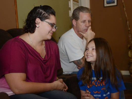 "ANI Fast Forward Program Ashton Bodiford (center), son of Angela (left) and Shawn (back, right) Brewerton, has been out of school for two weeks because his hair is ""too long"" according to school district policy. His mom finds fault with the rule.. Friday,"