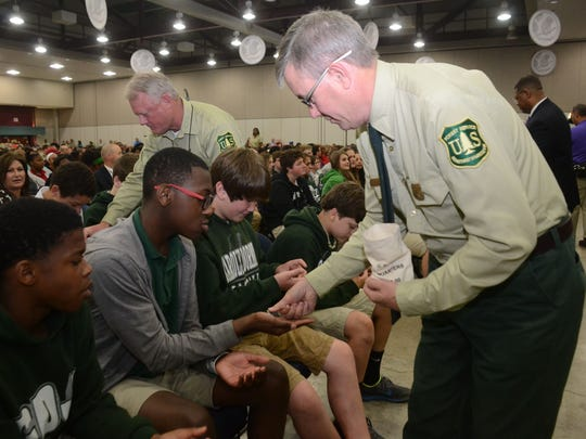 Eddie Taylor, U.S. Forest Service, (back, left) Kisatchie National Forest supervisor, and Tony Tooke, U.S. Forest Service Regional Forester, hand out quarters featuring the Kisatchie National Forest to local students attending the official quarter launch. Students under the age of 18 were each given a quarter at the event held Wednesday at the Riverfront Center in downtown Alexandria.