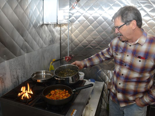 ANI Foodapalooza Gary Perkins, executive and business director for the business acceleration system which is part of the Central Louisiana Economic Development Alliance (Cleda), cooks winter squash (front) and a mixture of kale, mustard greens, bok choi an
