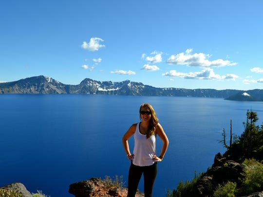 Reporter Alisha Roemeling stands at the edge of Crater Lake.