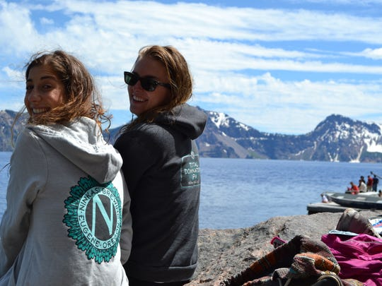 Emilie Hartvig and Alisha Roemeling sit on a large rock at the edge of Crater Lake overlooking the water in 2014.