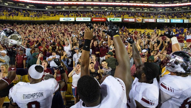 Troy players celebrate their team's 24-21 victory over LSU with Troy fans in an NCAA college football game in Baton Rouge, La., Saturday, Sept. 30, 2017. (AP Photo/Matthew Hinton)