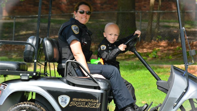 Six-year-old Peyton Gesing, seen here on patrol, is a cancer patient who was made an honorary member of the Simpsonville Police Department this summer.