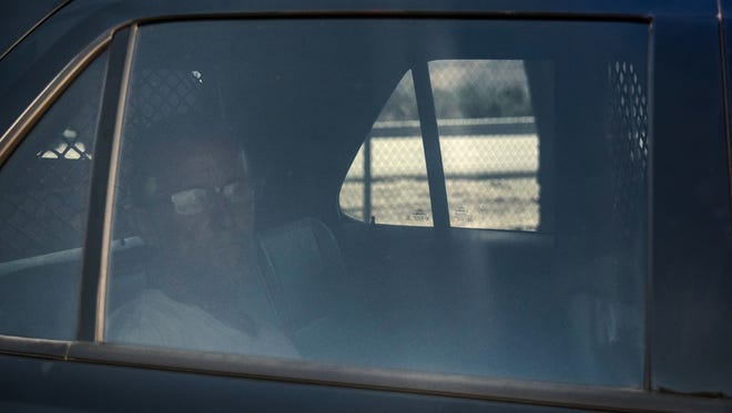 James Edgley, 48, who led authorities on a lengthy chase in an allegedly stolen semi truck, is photographed through the window of a patrol car on Tuesday.