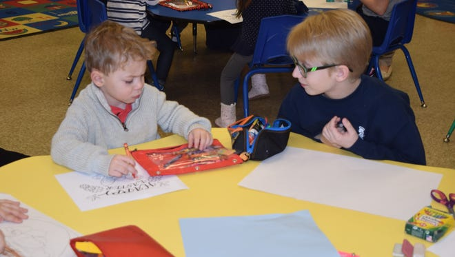 """Gavin Maines (left) and Joshua Mitchell work on """"Easter"""" placemats for Spirit and Truth Ministries as part of a school-wide day of service on Jan. 31 at St. Mary School."""