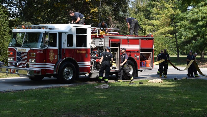 Indianapolis firefighters pack up damaged hose after a house fire in the 4200 block of Winding Way