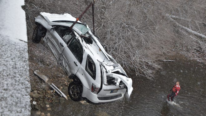 Emergency workers haul a Chevy Equinox out of the Fall Creek on Christmas Eve.