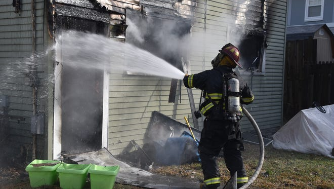 The Indianapolis Fire Department works to contain a house fire that left two dogs dead
