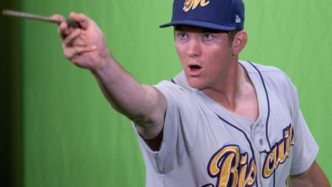Michael Russell pretends to cast a spell like Harry Potter during the Biscuits media day at Riverwalk Stadium.