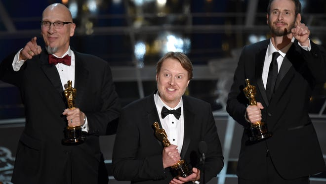 """Roy Conli, from left, Don Hall, and Chris Williams accept the award for best animated feature film for """"Big Hero 6"""" at the Oscars on Sunday, Feb. 22, 2015, at the Dolby Theatre in Los Angeles."""