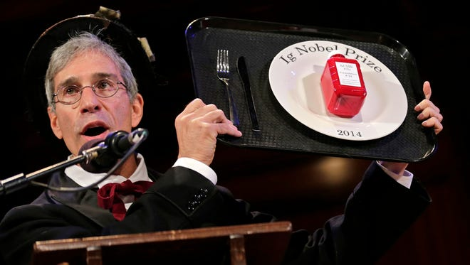 Master of Ceremonies Marc Abrahams holds up the 2014 Ig Nobel Prize trophy during a performance at the Ig Nobel Prize ceremony at Harvard University, in Cambridge, Mass.,Thursday.