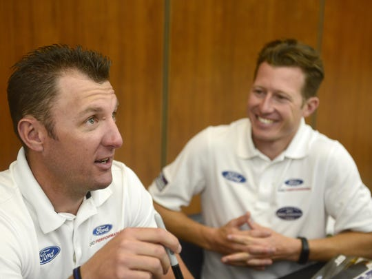 Ford GT drivers Joey Hand, left, and Ryan Briscoe sign autographs for Ford employees and contractors during a visit Friday to Ford World Headquarters in Dearborn.