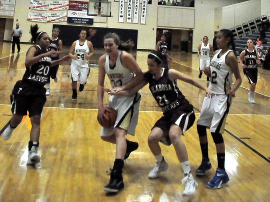 Ruidoso's Lia Mosher protects the ball at the basket.