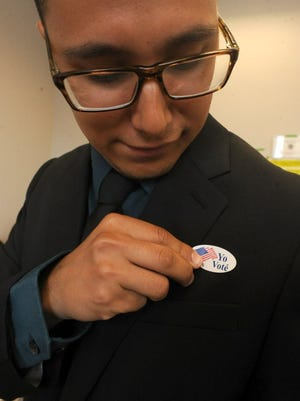 A voter puts a 'Yo Vote' '(I Voted) sticker on his lapel in this file photo.