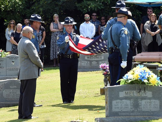 Arkansas State Police troopers fold the American flag that was draped over the casket of Marion County Sheriff Roger Vickers.