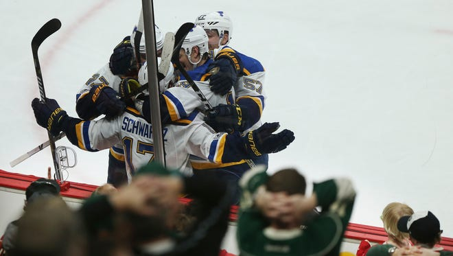 St. Louis Blues' Jaden Schwartz (17) is swarmed by his teammates after scoring a goal against the Minnesota Wild during the third period of Game 2 of an NHL hockey first-round playoff series Friday, April 14, 2017, in St. Paul, Minn.