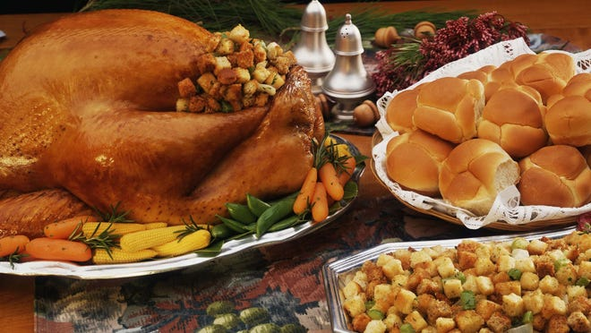A table is set with a festive Thanksgiving dinner.