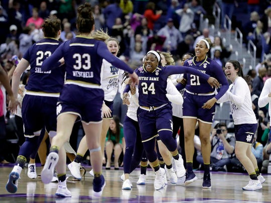 Notre Dame's Arike Ogunbowale (24) is congratulated by teammates after making the game-winning basket to defeat Connecticut in overtime in the semifinals of the women's NCAA Final Four college basketball tournament, Friday, March 30, 2018, in Columbus, Ohio. Notre Dame won 91-89. (AP Photo/Ron Schwane)