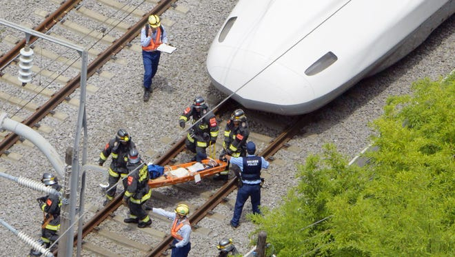 A passenger is carried out of the bullet train, right, which made an emergency stop in Odawara, west of Tokyo, June 30, 2015.