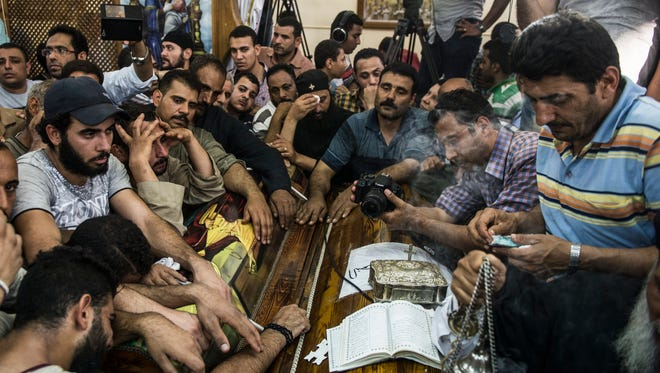 Relatives mourn over a coffin during the funeral of victims killed in an attack at the Monastery of St Samuel the Confessor, in Minya Province, central Egypt, May 26, 2017.