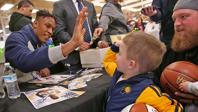 Standing with his father Jordan Taylor, right, and brother Hux Taylor, not pictured, Easton Taylor, center, gives a high five during an autograph session with Indiana Pacers player Myles Turner at Kroger, Friday, January 29, 2016, promoting Turner's WARM (We All Really Matter) program.  Fans received a bag of items to give to someone in need during the winter season.  Fans also received 2 tickets to an upcoming Pacers game and an autograph from Myles.